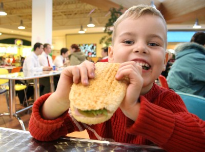 Happy Boy In Cafeteria Eating Sandwich